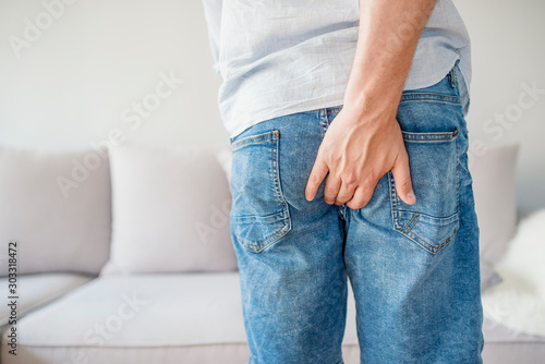 Young man has pain in the butt, Hemorrhoids, Anal disorders. Canvas Print