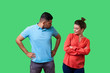 canvas print picture - Portrait of resentful dissatisfied couple in casual wear standing together, looking arrogant at each other and arguing, misunderstanding in relations. isolated on green background, indoor studio shot