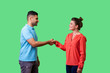 canvas print picture - Portrait of positive friendly man and woman in casual wear standing, smiling at each other and shaking hands, couple first meeting or acquaintance. isolated on green background, indoor studio shot