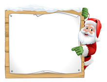 Santa Christmas Cartoon Character Peeking Around A Wooden Sign And Pointing At It