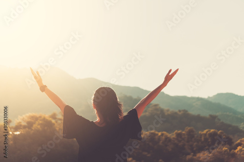 Copy space of woman rise hand up on top of mountain and sunset sky abstract background.