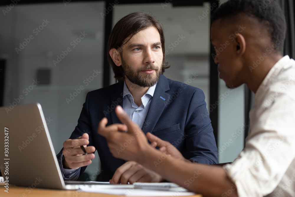 Fototapeta Focused businessman listening to young african american employee.