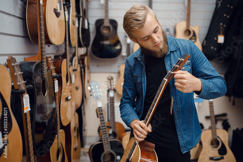 Poster Magasin de musique Bearded young man choosing a guitar in music store