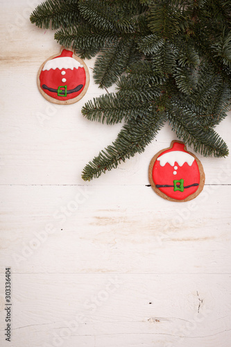 Top view of christmas cookies in the shape of balls on a wooden background with sprigs of evergreen spruce Wallpaper Mural