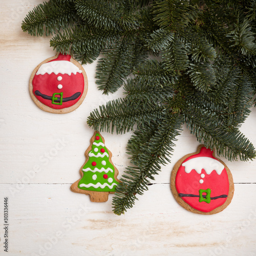 Top view of christmas cookies in the shape of balls and christmas tree on wooden background with sprigs of evergreen spruce Canvas Print