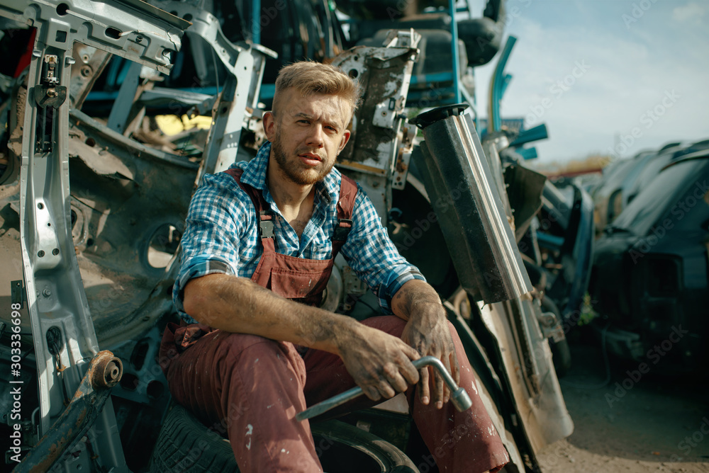Fototapety, obrazy: Dirty male repairman with wrench on car junkyard