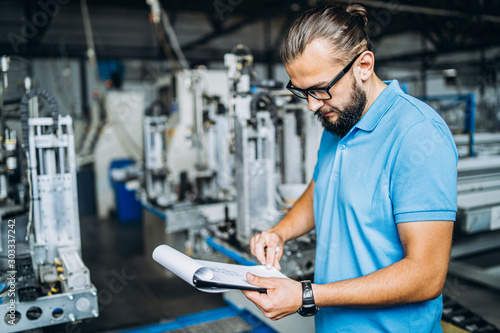 Cuadros en Lienzo  A worker in glasses standing near industrial equipment and verifies production data