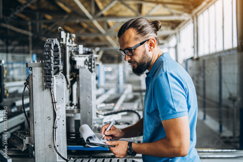 Fotografía  A worker in glasses standing near industrial equipment and verifies production data