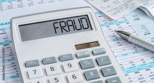 A calculator with the word Fraud on the display Fotobehang