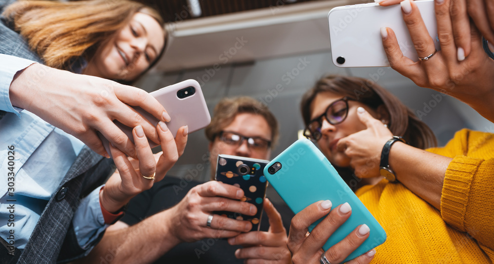 Fototapeta Group of business people stand in line hold smartphone. Wide shot. Positive office employees standing together and holding phone in hands