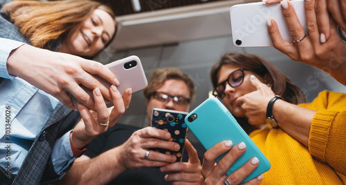 Obraz Group of business people stand in line hold smartphone. Wide shot. Positive office employees standing together and holding phone in hands - fototapety do salonu