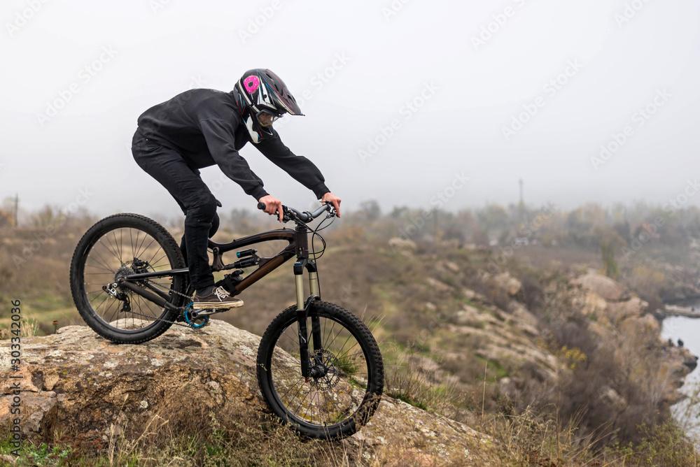 Fototapeta Mountain biker rides a bicycle on the rocks, extreme sport.