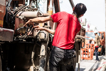 Back View Of Truck Crane Driver Wearing Red T-shirt Is Controlling Crane Working On Electric Power Poles.