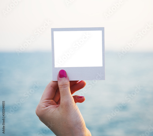 Obraz Woman female hand holding closeup blank instant square photo photograph with white copy space to distant horizon. Sea ocean water sky in distance bokeh background backdrop. Pink fingernail nail polish - fototapety do salonu