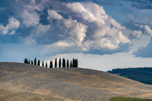 Beautiful Tuscany Landscape With Blue Sky, Cypress Trees Beyond The Hill And Clouds