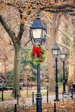 New York City Street Light Decorated With Pine Garland And Red Ribbon For Christmas During Holiday Season