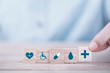 canvas print picture Hand chooses a emoticon icons healthcare medical symbol on wooden block , Healthcare and medical Insurance concept