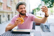 Young Man Having Burger In Restaurant Outdoors And Taking Selfie