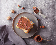 Bread Toast With Chocolate Cream Butter, Jar Of Chocolate Cream On The Concrete Background