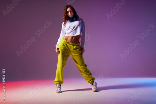 Pretty attractive female standing on white floor of dance studio, looking at cam Canvas Print