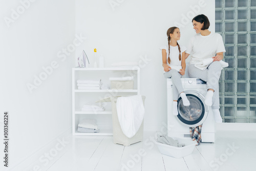 Obraz na plátně  Housewife and small child sit on top of washing machine, holds freshly washed to