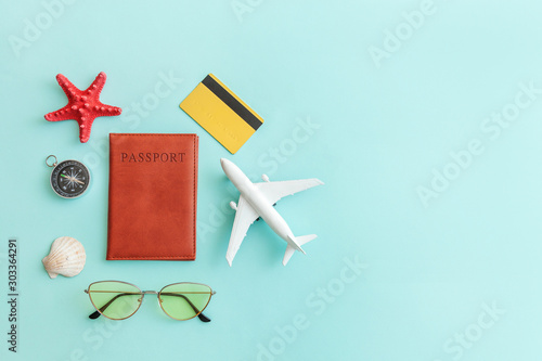 Obraz Vacation travel adventure trip concept. Minimal simple flat lay with plane passport sunglasses compass gold credit card shell on blue pastel colourful trendy background. Tourist essentials - fototapety do salonu