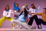Teenage girl dancing hip-hop on modern dance studio, sitting on floor in white pants, spreading hands up, looking straight, training before concert