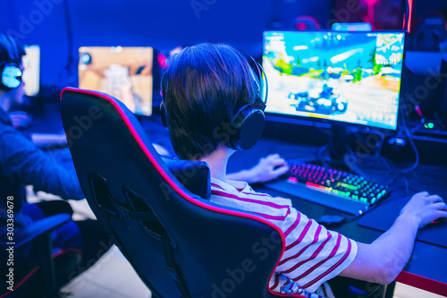 Cuadros en Lienzo  Professional gamer playing tournaments online video games computer with headphon