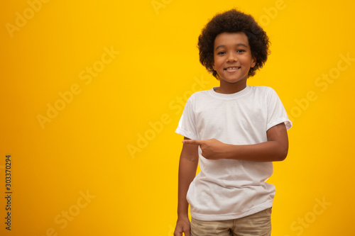 African American boy with black power hair on yellow background Canvas Print