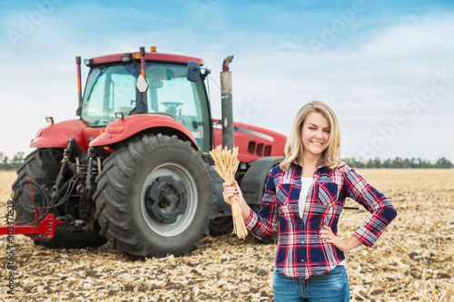 A young woman in a field on a background of a tractor with spike of wheat in her hands.
