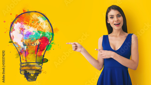 Obraz Young woman pointing at big stylized light bulb on yellow background. Concept of idea and creativity - fototapety do salonu