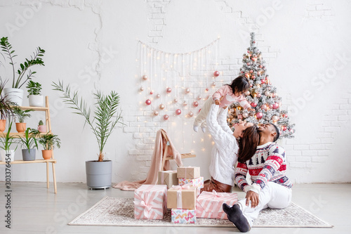 Leinwand Poster  Happy mixed race family african american dad mom and daughter rejoice celebrating Christmas sitting on living room floor in beautiful bright interior with Christmas tree and decorations