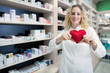 Healthy heart concept. Heart disease and cardiovascular problems. Female pharmacist holding heart and promoting cardiovascular medications and successful treatment.