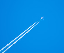EasyJet Airplane Flying At High Altitude Leaving Its White Wake Over Blue Sky