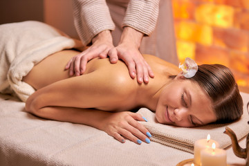 Obraz na płótnie Canvas Attractive young female get massage on back lying on table in spa salon, naked back. female hands doing massage, using candles