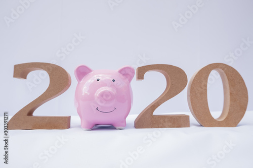 Fototapeta pink piggy bank with 2020 wooden character, set business goals with new plan on 2020 obraz