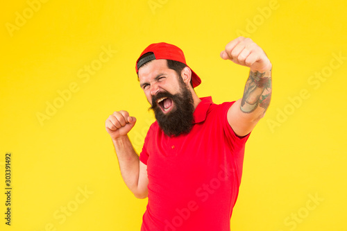 Obraz happy emotional guy. male summer fashion. Barber salon and facial hair care. being trendy and brutal. Beard and mustache grooming. happy mature hipster yellow backdrop. bearded man celebrate success - fototapety do salonu