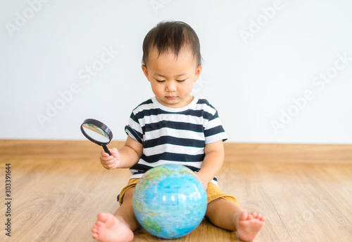 Photo  Asian chinese baby boy Looking At Globe Through Magnifying Glass at home on white Background