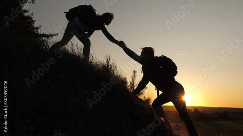 Fotografie, Obraz A male traveler holds out his hand to a female traveler climbing a hilltop