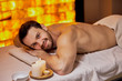 canvas print picture - Handsome caucasian lying after massage in the beauty salon, spa salon, naked skin. Young bearded man relaxing,yellow wall background in spa