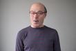 Senior man in huge glasses in being surprised. Wow is it really true. Studio shot. Posititve facial human emotion.