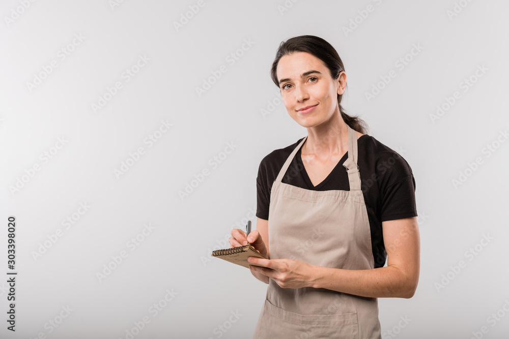 Fototapeta Pretty young brunette waitress in apron making notes about order in notepad