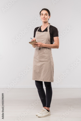 Fotografia Pretty young waitress of cafe making notes about order of client in isolation
