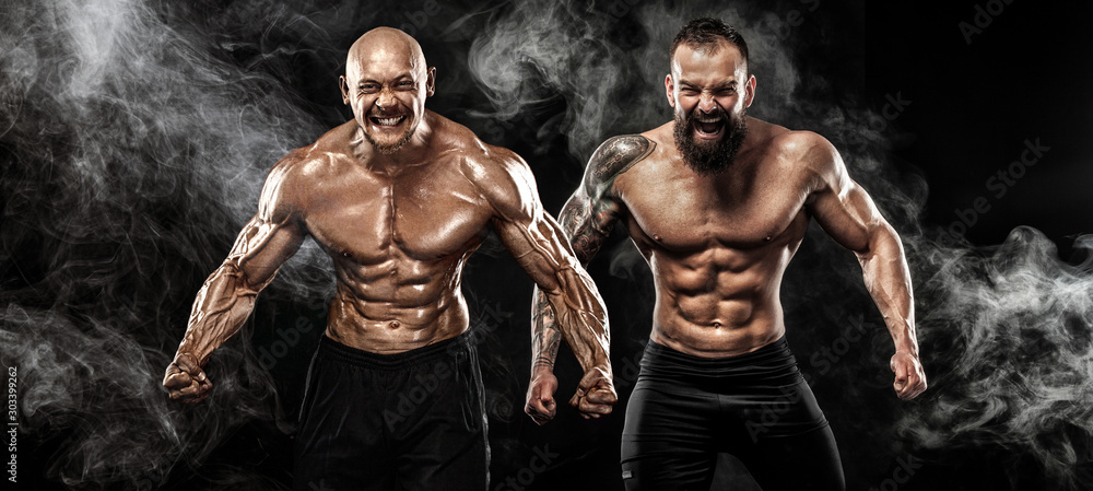 Fototapeta Sport and fitness concept. Two wild sportsmen boxers and bodybuilders posing on black background with smoke before competition or fight. Copy Space.