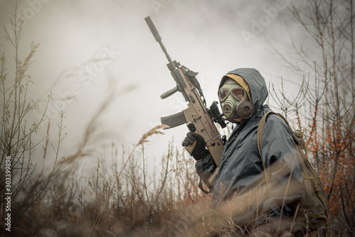 Cuadros en Lienzo  Soldier with rifle in raincoat and gas mask is walking outdoor.