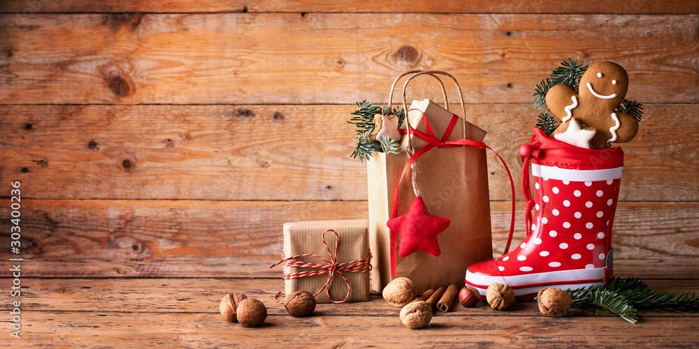 Fototapeta Santa´s shoe  -  Stuffed Santa Claus boot -  Gumboot,  paper bag, gift boxes and gingerbread man on rustic wood background  -  Christmas card