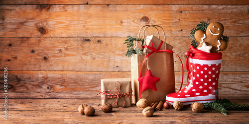 Santa´s shoe  -  Stuffed Santa Claus boot -  Gumboot,  paper bag, gift boxes and gingerbread man on rustic wood background  -  Christmas card  - 303400236