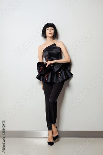 Fotografía Beautiful girl in tight pants and peplum silk corset posing near white wall, she