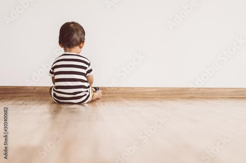 Fototapeta Back view of Little baby boy sitting alone and watching smartphone. obraz na płótnie