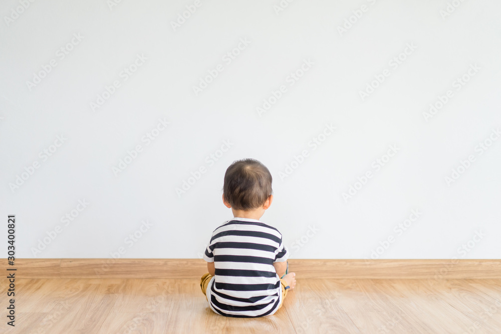Fototapeta Back view of Little baby boy sitting alone and watching smartphone. - obraz na płótnie